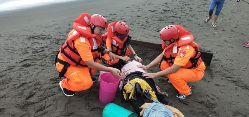 海巡人員協助救援擱淺瓜頭鯨。(記者吳仁捷翻攝)