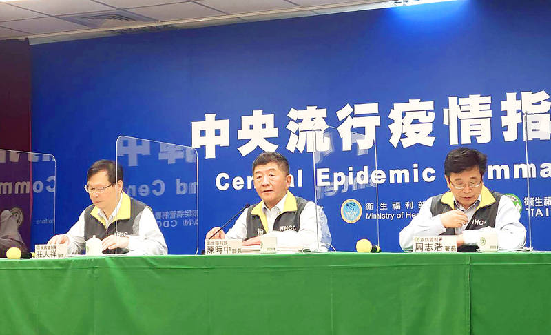 Minister of Health and Welfare Chen Shih-chung, center, discusses the temporary suspension of government-funded influenza vaccines for people aged 50 to 64 at a news conference in Taipei yesterday. Photo: CNA