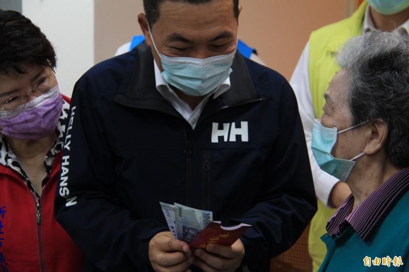 新北市長侯友宜(左)發放重陽禮金給88歲的阿嬤陳朱淑瑛(右),也提醒她要照顧健康。(記者邱書昱攝)