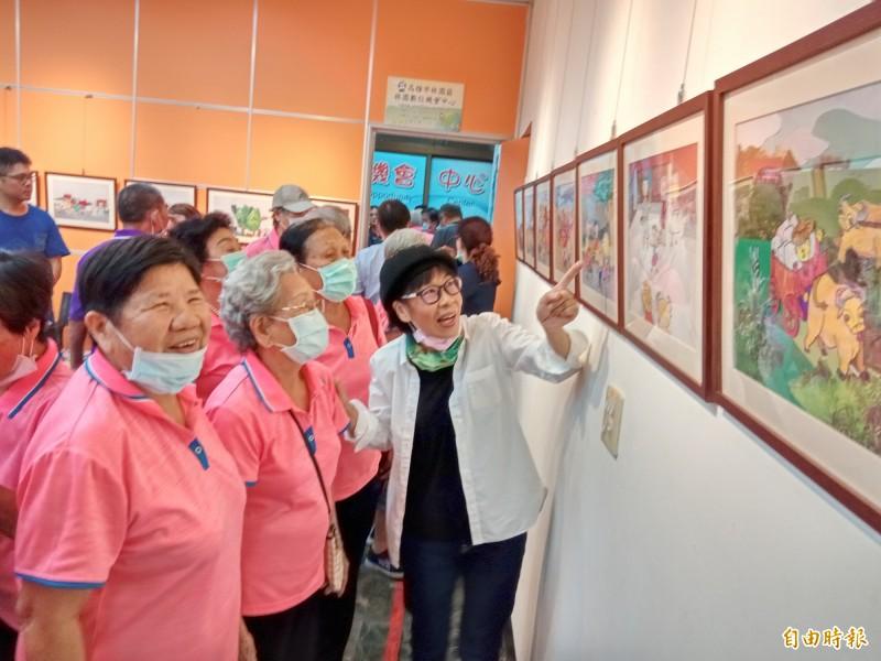 繪本美術指導老師許錦治(右1)向潭頭社區長輩導覽繪本原圖。(記者洪臣宏攝)