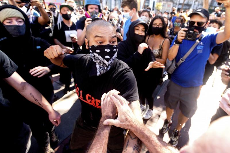 蒙面的激進左派人士,17日在舊金山出拳毆打抗議推特言論審查的人士。(美聯社)