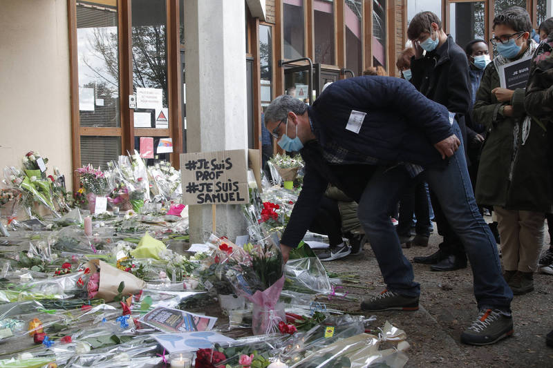 法國反恐檢察官及警方公布斬首案最新調查進度。圖為法國群眾獻花致意帕蒂。(美聯社)