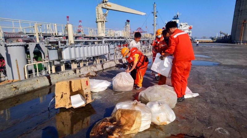 「台安2號」加油船燃油外漏,因風浪大拍到岸上,污染台中港29號碼頭,海巡等人員正以吸油等設法去除油污。(記者歐素美翻攝)