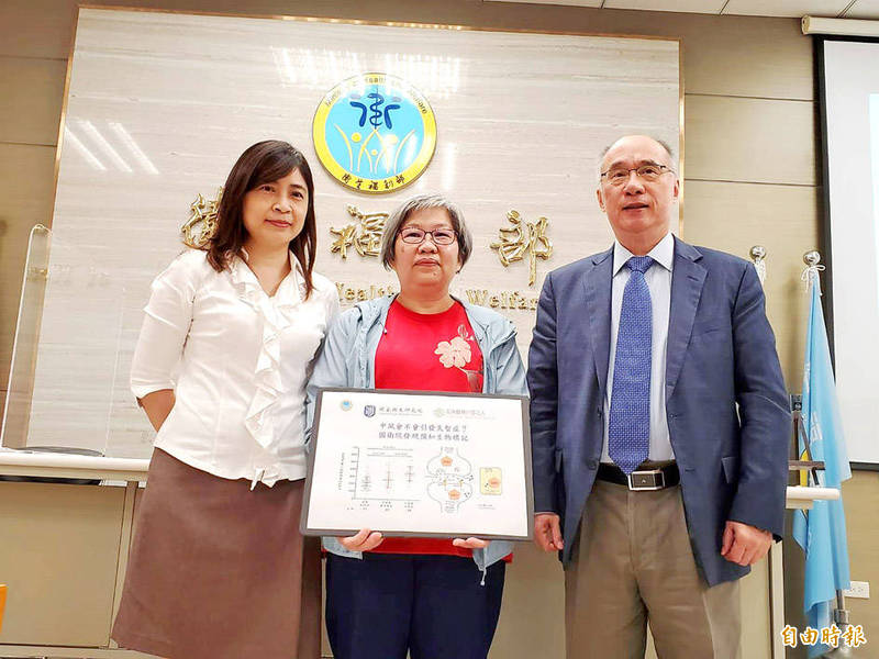 From left, Chen Yi-chun, a physician at Linkou Chang Gung Memorial Hospital's Department of Dementia, Liu Yu-li, a researcher at the National Health Research Institutes' (NHRI) Center for Neuropsychiatric Research, and NHRI president Liang Kung-yee pose for a photograph after a news conference at the Ministry of Health and Welfare in Taipei yesterday. Photo: Lin Hui-chin, Taipei Times
