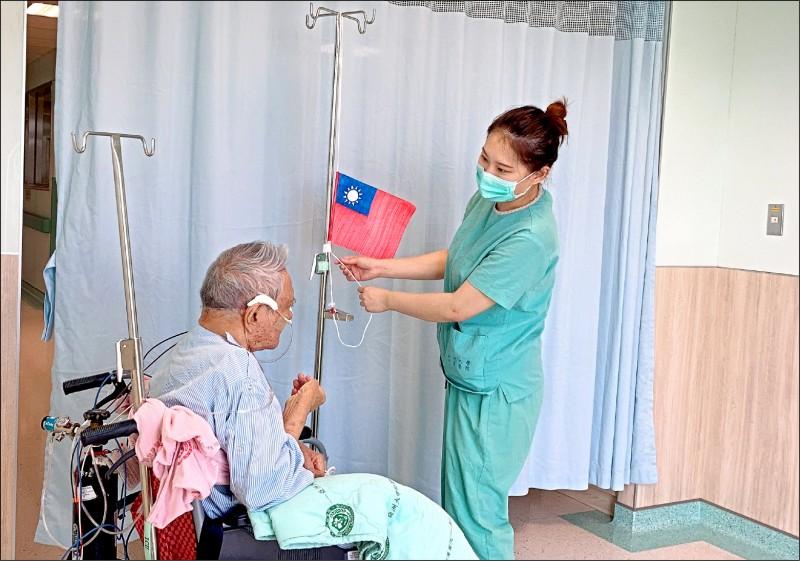 護理師陳俞廷(右)自製國旗,利用點滴架,為白姓退休老師(左)舉行「升旗大典」。(記者陳建志翻攝)