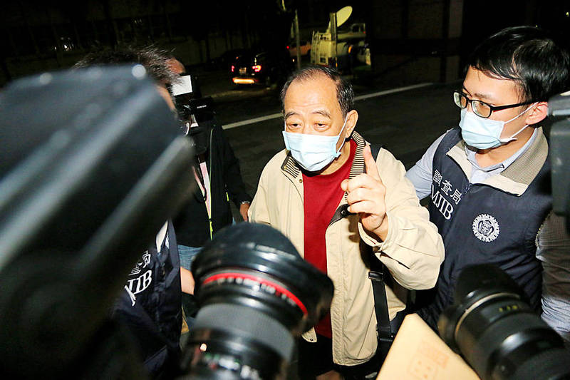 Former Military Intelligence Bureau colonel Chang Chao-jan talks to reporters yesterday while being escorted by a Ministry of Justice Investigation Bureau officer at the Taipei District Prosecutors' Office. Photo: CNA