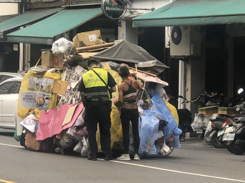 赤膊哥陳男推溢出推車的回收物被喻「移動城堡」,回收物高過他和警察許多,今年迄今遭警方開單10次。(記者黃良傑翻攝)