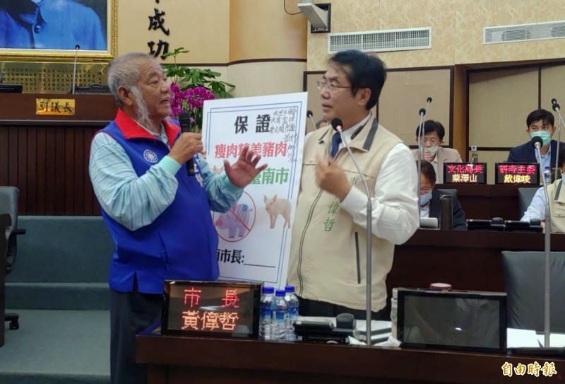 議員張世賢(左)要市長黃偉哲(右)簽署承諾。黃則強調,他會依議會的決議來執行,並強調他只吃本土豬肉,也會嚴格來把關。(記者蔡文居攝)
