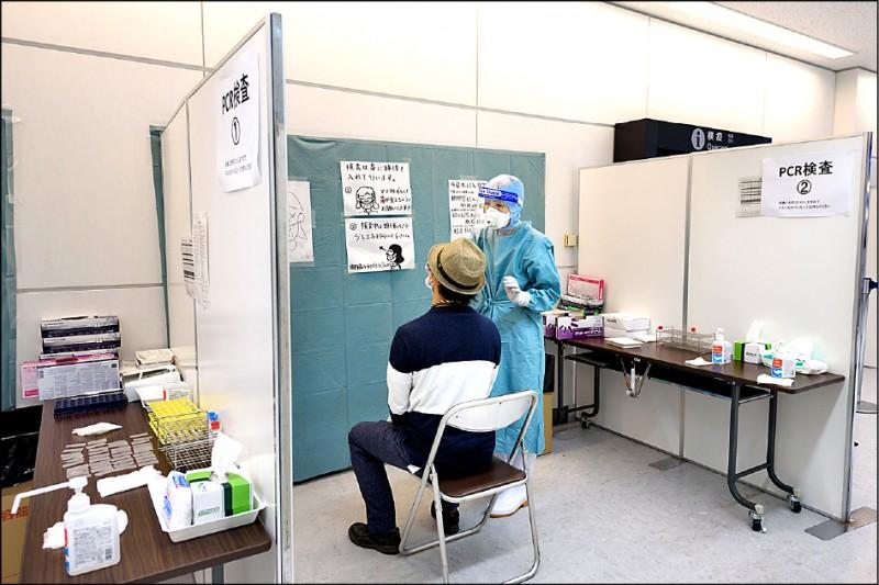 台人赴日檢出3例陽性,其中2例在台採陰,疫情指揮中心研判,在日檢驗可能是「偽陽性」。圖為日本成田機場採檢站。(彭博檔案照)