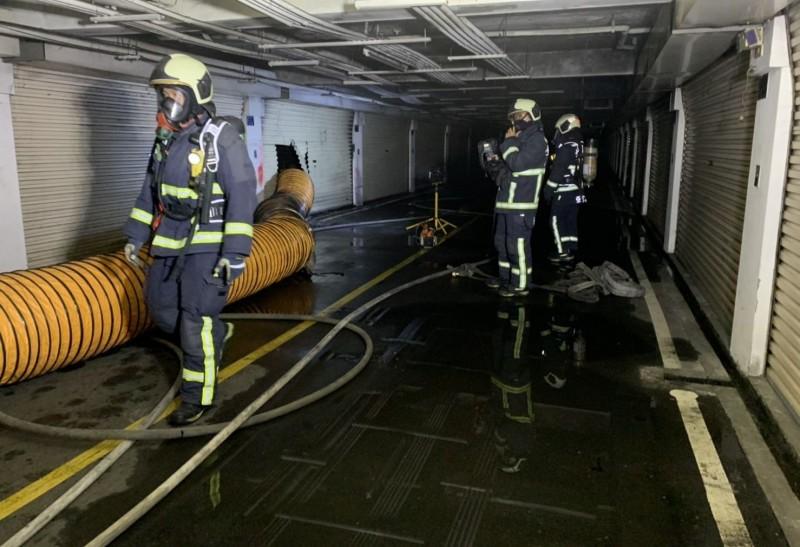 台中霧峰四德路一處社區地下室車庫起火,消防人員破壞鐵捲門進行搶救。(記者陳建志翻攝)