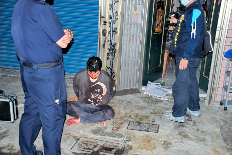 凶嫌當場被警方逮捕,蹲坐地上,身上也沾滿血跡。(記者楊金城翻攝)