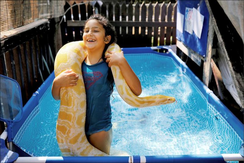 以色列8歲女童英芭,以及從小和她一起長大的寵物蟒「貝兒」。(路透檔案照)