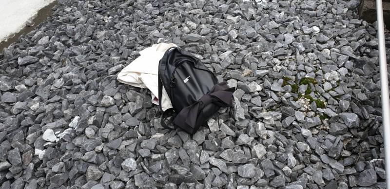 墜樓女子遺留在現場的背包。(記者劉慶侯翻攝)