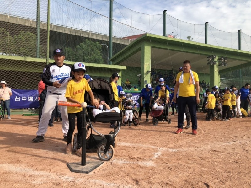 身障小選手在小幫手的協助下完成擊球、跑壘,即使在推車中也能享受騁馳球場的快感。(台中市運動局提供)