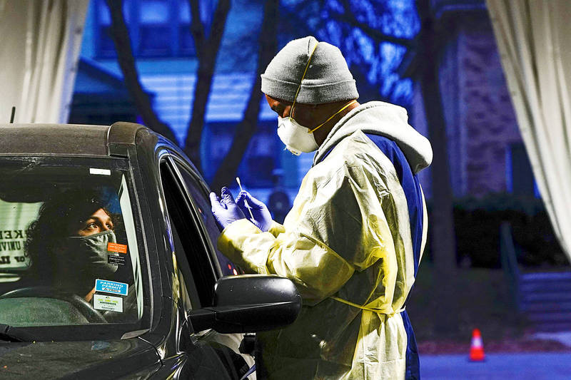 A medical worker prepares to collect a nasal swab at a drive-thru testing site outside the Southside Health Center in Milwaukee, Wisconsin, on Wednesday.   Photo: Reuters