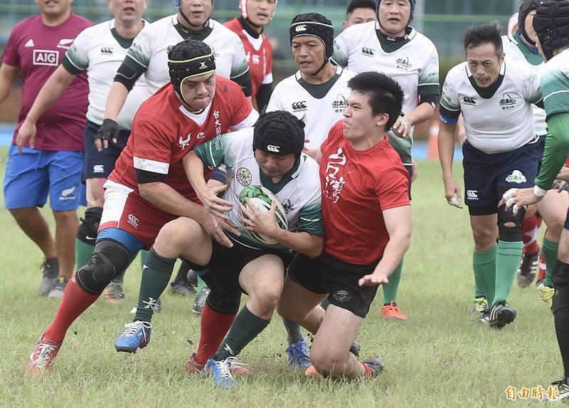 台灣大學橄欖球隊75週年慶24日在台大田徑場舉行,現職資深或主任醫生組成的台大醫橄(紅衣)與台大校友隊友誼賽,雙方全力以赴,充滿運動精神。(記者簡榮豐攝)
