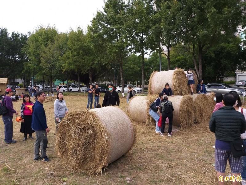 竹北新瓦屋的「水稻田生態教育園區」內正在進行的稻草故事屋活動上,大人小孩都瘋狂跟大草捲「同框」。(記者黃美珠攝)