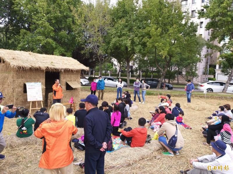 竹北新瓦屋的「水稻田生態教育園區」內的稻草故事屋,大人小孩坐在草捲上聽故事。(記者黃美珠攝)