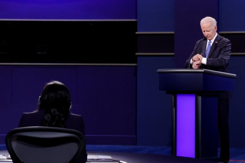 22日辯論會上,當主持人提醒斷川普「時間快不夠了」,拜登竟抬起手錶確認時間,當時距辯論結束還10分鐘。網友後來發現,拜登講台上放了平板電腦。(法新社)