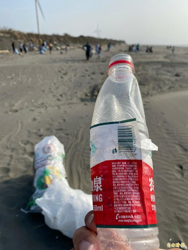 在雲林四湖沙灘淨灘撿到中國產的礦泉水瓶,學童驚呼,這一瓶飄洋過海6、700公里。(記者黃淑莉攝)