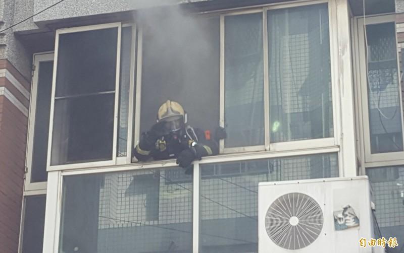 台中大里成功路一間麵店今天上午起火,消防人員進屋搜尋,趕緊將窗戶卸下協助排煙。(記者陳建志攝)