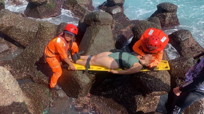 岸巡隊員將受傷的許女搬運上岸(記者吳昇儒翻攝)