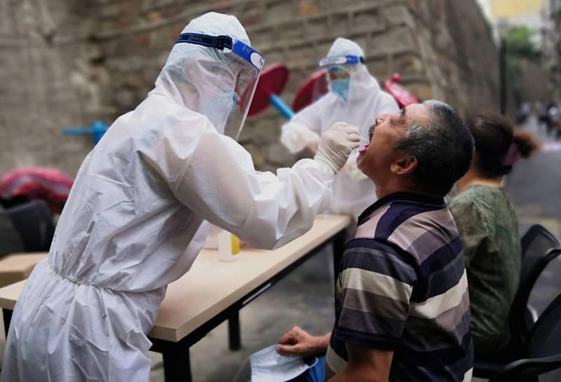 中國新疆喀什地區25日檢出137例武漢肺炎(新型冠狀病毒病,COVID-19)無症狀感染者,因為原先僅1例無症狀感染,而今卻一夕暴增,引發當局緊張。圖為新疆的醫療人員對民眾進行核酸檢測。(路透資料照)