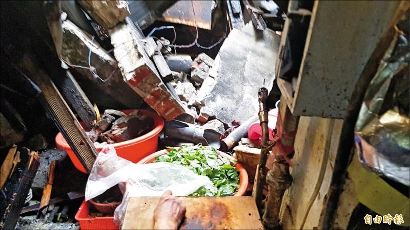 嘉義市東市場一處攤位遭掉落的頂樓磚牆砸毀,造成攤商夫妻受傷送醫。 (記者林宜樟攝)