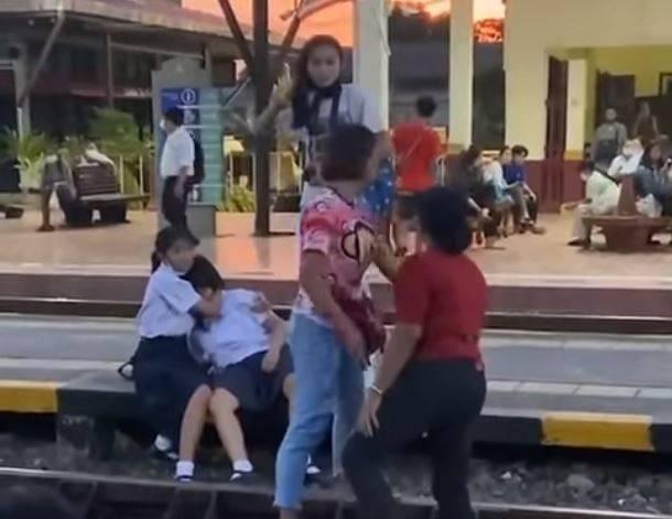 泰國一名少女(左二)由於未在車站播放泰國愛國歌曲《頌聖歌》時,起立向泰國王室致敬,而遭一名愛國大媽(紅衣婦人)扯頭髮、搧耳光。(圖擷取自臉書_ซีนิว วิวเว่อร์ 4K)