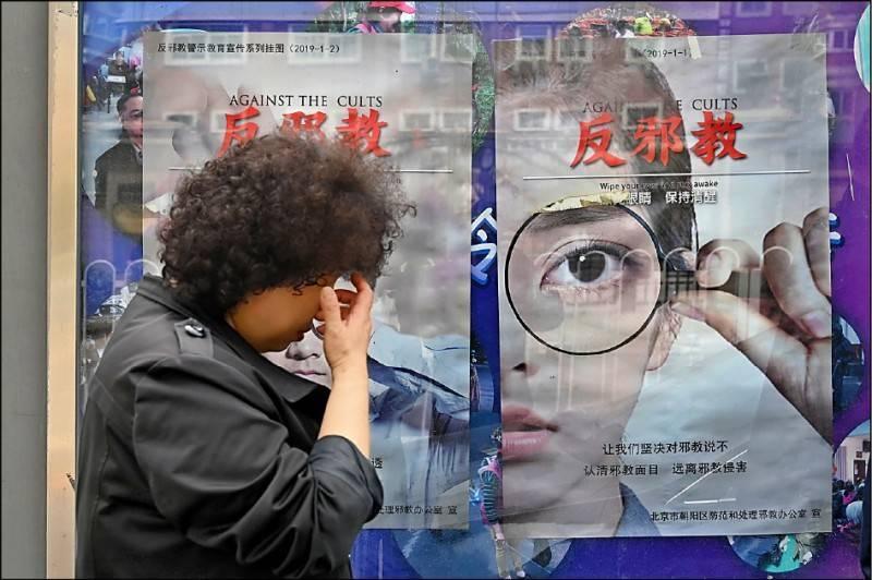 圖為中共政權打壓宗教自由,曾大舉徵求「反邪教」宣傳海報創作,張貼在首都北京等地街頭。(資料照,法新社)