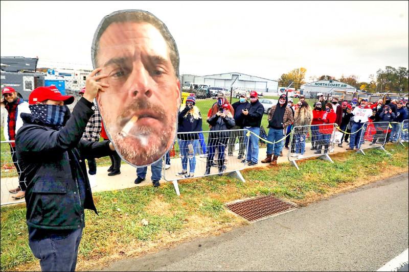 賓州的川普支持者廿日在造勢會場等待川普抵達前,高舉民主黨總統候選人拜登兒子杭特的大幅人頭照。(路透)