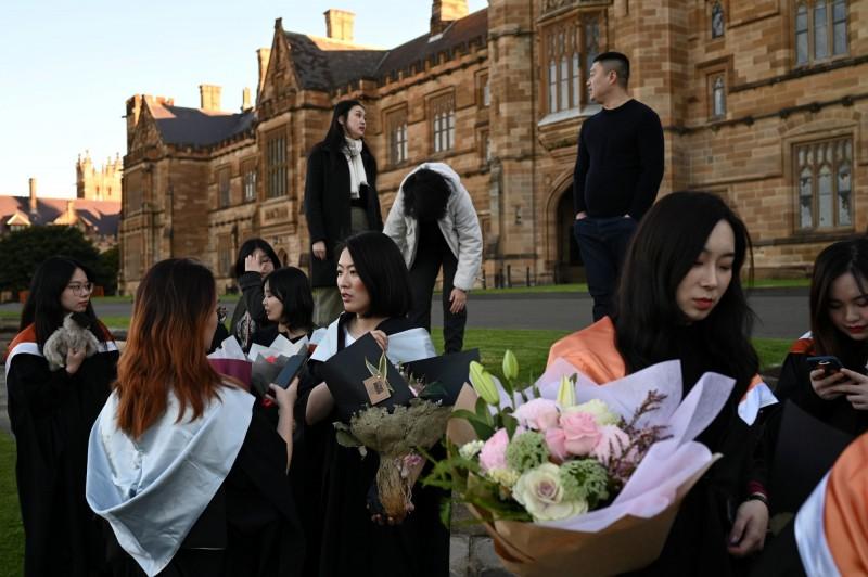 中國政府監控海外留學生,甚至以家人相要脅,要求他們臥底「戴罪立功」。圖為澳洲雪梨大學的中國留學生參加畢業典禮,圖中人物與本新聞無關。(路透檔案照)