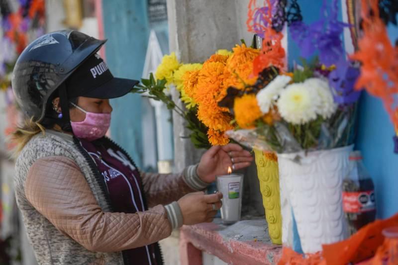 疫情仍在墨西哥延燒,使得當地民眾被迫提前及縮小亡靈節過節規模。圖為墨西哥一名女性提前探視、用萬壽菊妝點親友墳墓。(法新社)
