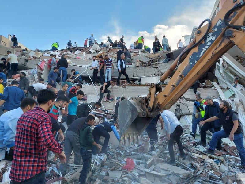 土耳其伊茲米爾市多棟建築物被震垮,救難人員和民眾合力在瓦礫堆中搶救。(路透)