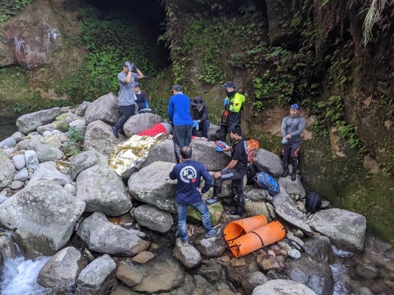 59歲陳姓婦人今天與80多名登山同好一起攀爬瑞芳小錐麓登山步道時墜谷,新北市第六救災救護大隊動員瑞芳分隊27名消防隊員入山,花了4個多小時,將她的遺體揹出來。(記者林嘉東翻攝)