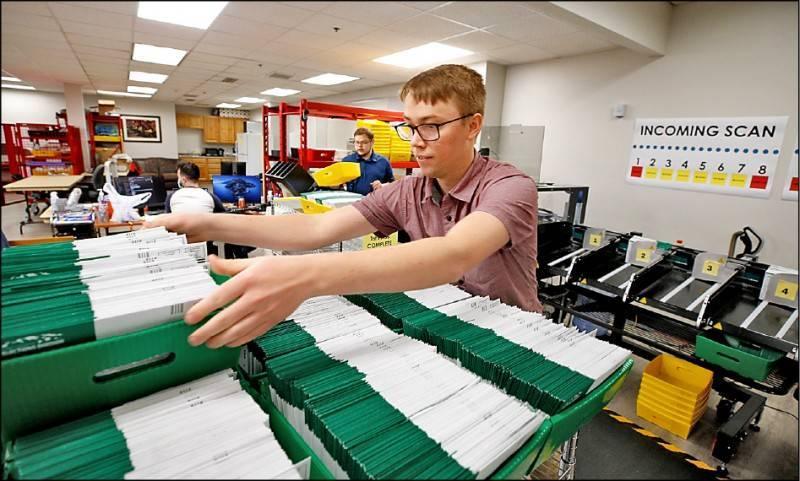 圖為猶他州普若佛(Provo)的選務人員,廿六日加緊整理郵寄投票的信件,以便屆時順利開票。(法新社)