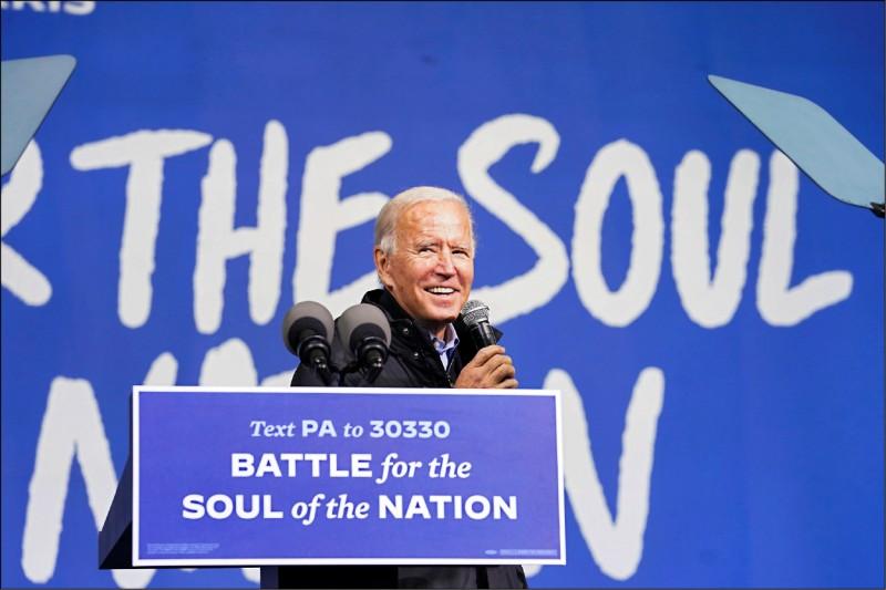民主黨總統候選人拜登一日鎖定關鍵「搖擺州」之一的賓州,在該州第一大城費城舉辦造勢活動。講台前方的看板寫著「為國魂而戰」。(路透)