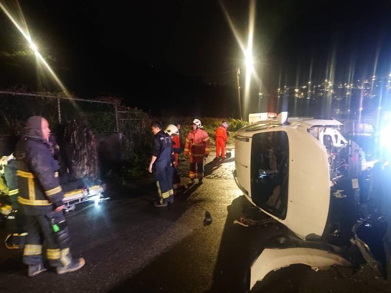 台2線濱海公路陰陽海路段,今天深夜發生轎車自撞橋墩翻車意外,消防隊員獲報將受困車內的簡男救出。(記者吳昇儒翻攝)
