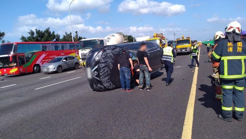 國道1號南向中壢路段今天下午發生追撞車禍,圖中黑色轎車被賓士車追撞後90度翻車,車上2人受傷。(記者李容萍翻攝)