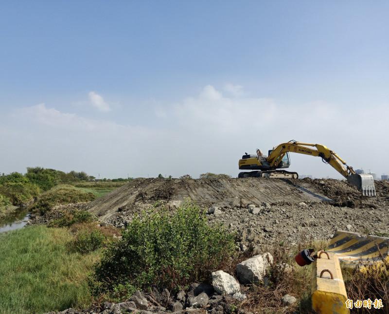 私人魚塭地被占用堆置土方(圖中怪手位置),施工廠商義力營造正持續進行清理作業。(記者王姝琇攝)