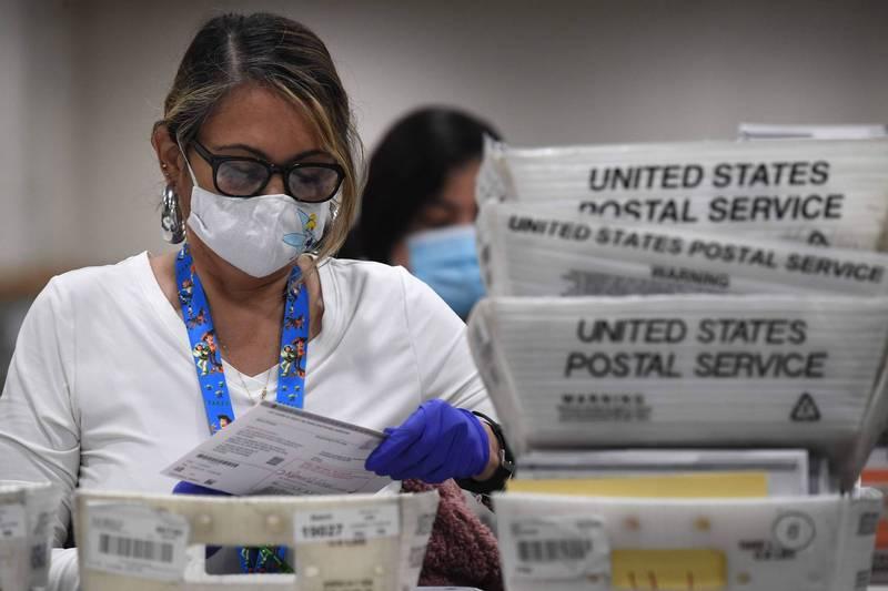 選情疫情齊升溫,美國單日確診首破12萬。圖為帶著口罩處理郵寄選票的人員。(法新社)