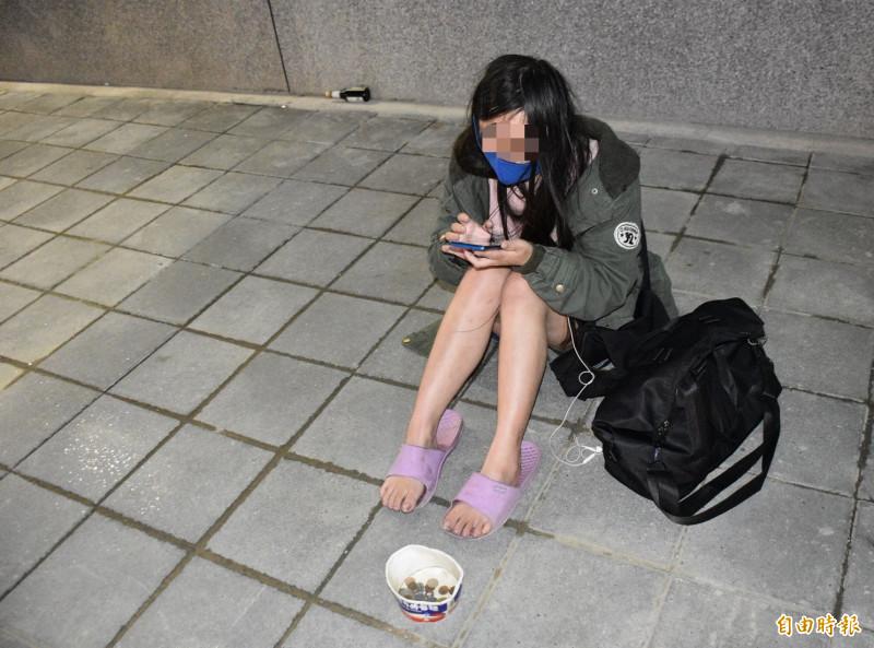 沈女坐在中壢火車站新啟用的跨站天橋旁,改口已經在上網找「工作」了。(記者李容萍攝)