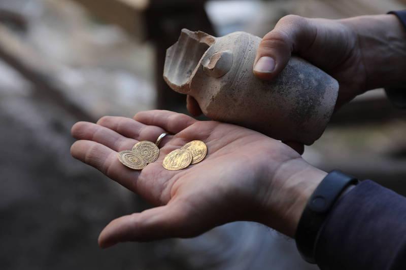 以色列古物局在耶路撒冷舊城區出土了一個小陶罐,裡面還裝有4枚金幣。(歐新社)
