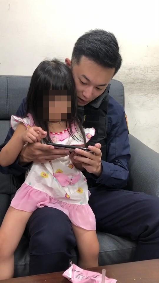 警員藍子其陪同女童看卡通,安撫她的情緒(記者吳昇儒翻攝)