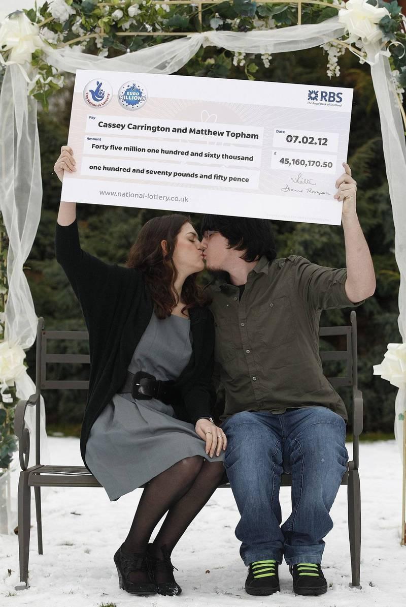 托普漢(Matt Topham)23歲時中了4500萬英鎊(約17億台幣)的樂透,如今卻因危險駕駛造成一人死亡,一人重傷。圖為托普漢(右)與妻子(左)拿著支票合影。(歐新社)