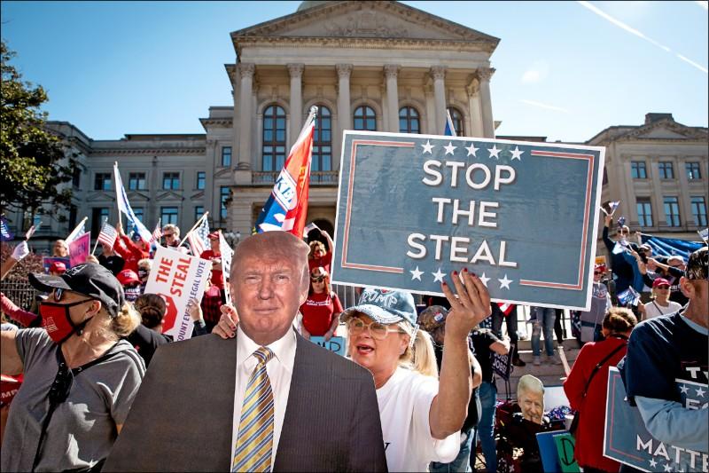 美國喬治亞州的川普支持者十四日手持「停止偷竊(選舉)」標語,在首府亞特蘭大的州議會外抗議,不滿媒體推估川普沒能拿下該州。(彭博)
