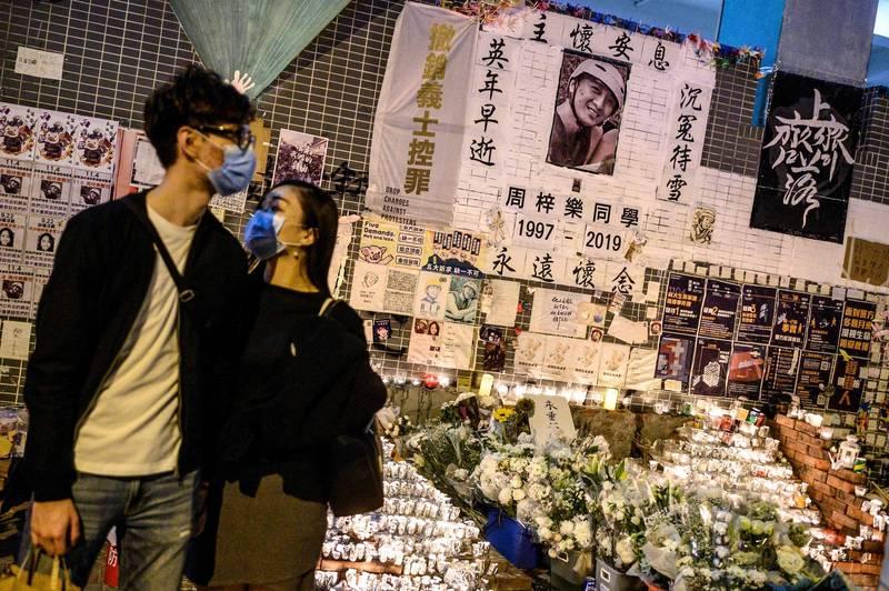 周梓樂的父親周德明今日首度公開接受媒體訪問,指出周梓樂最後傳給他的訊息,提醒他關好窗門,以免催淚煙霧飄入家中。圖為香港市民自發為周梓樂立祭壇悼念。(法新社)