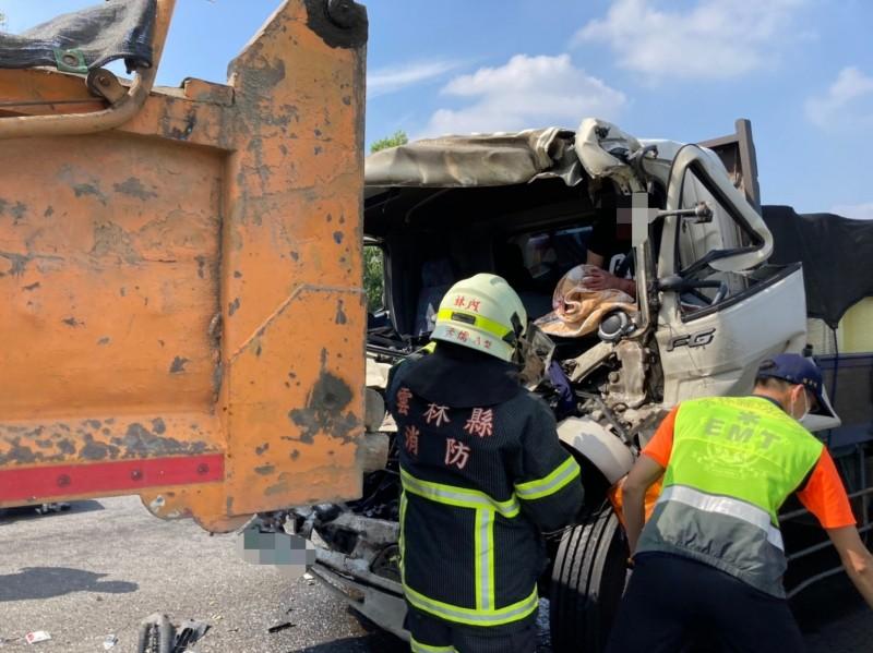 國道3號南下261公里處今天11點左右發生大貨車追撞砂石車事故,大貨車車頭扭曲變形,駕駛受困車內動彈不得,雲林縣消防局救護人員搶救中。(記者黃淑莉翻攝)