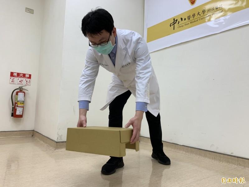 醫師楊宗熹指出直接彎腰搬物口,容易損傷脊椎。(記者蔡淑媛攝)