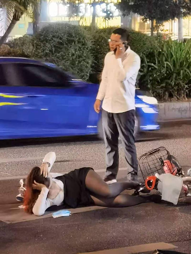 可見該名OL倒在馬路上,身邊站著一名似為肇事車主,正在打電話的男子。(擷取自爆廢公社公開版)